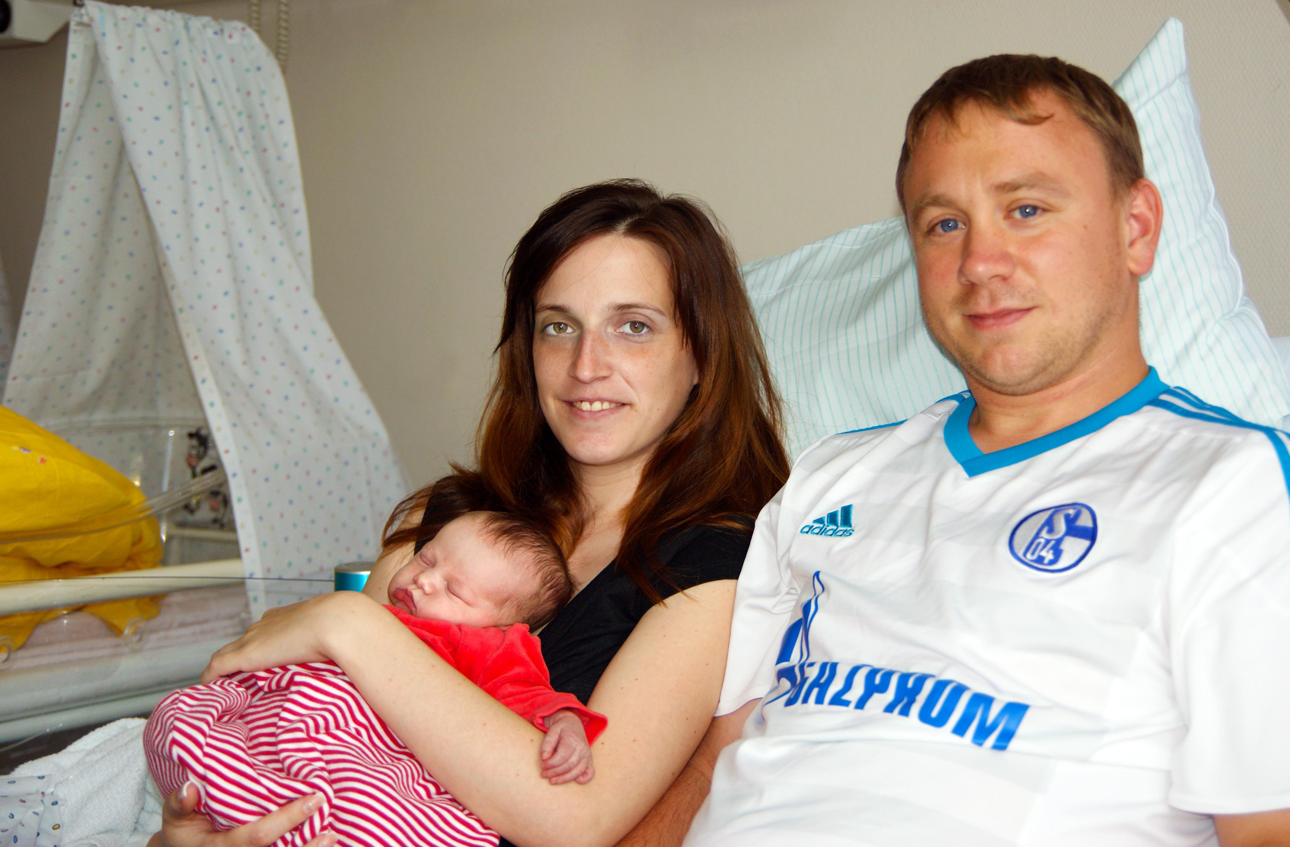 Baby in den Armen seiner Eltern.