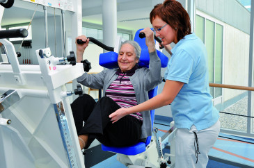 Patientin beim Krafttraining im Therapieraum der Geriatrischen Rehaklinik
